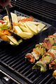 This image depicts freshly-prepared kabobs (Lt), w