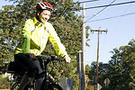 This photograph depicts a smiling female bicyclist
