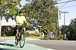 This photograph depicts a smiling male bicyclist,