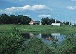 Red canoe with fisherman on a pond with a red barn