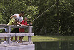 Family fishing from a bridge at a local pond
