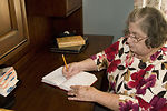 Seated at her in-home desk after having picked up