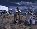 Nancy Harms and Dylan Prichertt portray pioneer woman and a black pioneer trading a fur at an Oregon Trail wagon encampment.