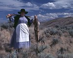 Nancy Harms portrays a woman pioneer with a rifle and a coyote pelt.