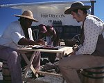 Dylan Prichertt, Rebecca Crow, and Brandon Kames portrqay oregon Trail Pioneers at a wagon encampment.