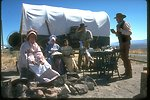 A presentation of living history with a pioneer family sitting outside of their covered wagon eating food at their dining table in the middle of the range land.