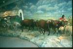 Exhibit at the NHOTIC of early Oregon settler herding sheep and oxen pulling his covered wagon.