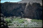 Large cliffs with a rock shelter in the middle are surrounded by sagebrush.