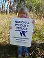 Girl Holding National Wildlife Refuge Sign