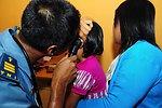 A Tentara National Indonesian Medical Professional Examines a Girl's Ear