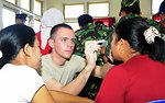 Army Spc. Lemoine Examines an Indonesian Medical Patient's Eyes