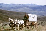 Covered wagon and pioneer on Oregon Trail. NHOTIC 10th Anniversary, wagon train reenactment.