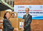 Dr. Nguyen Thu Thuy (left), Deputy Director General, Department of Animal Health under Vietnam's Ministry of Agriculture and Rural Development, receives a box of the personal protective equipment from USAID Mision Director Joakim Parker (right).