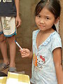 A young girl receives a USAID pen during an animal health worker training in Quang Tri Province.
