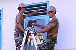 Builder 3rd Class Robert Woodley and Utilitiesman Anthony Sheffield Paint Window Trip on the In-Patient Ward of the Daruba Hospital Engineering Site