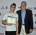 U.S. Ambassador David Shear presents Vietnamese rapper, Karik, with a certificate of appreciation for taking parting in the MTV EXIT concert against human trafficking and exploitation