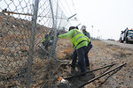 Repairing security fence at construction site