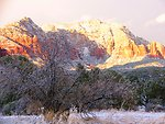 A majestic scene of sandstone mountains dusted with snow and valley oaks and pinion pines