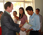 USAID Mission Director Francis Donovan gives certificates to teachers at the graduation ceremony