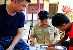 Command Master Chief, Master Chief Hospital Corpsman (SW/FMF) Noel Manlapaz and Master Chief Culinary Specialist (SW/AW) Jack Fong Piece Togther a Puzzle With an Indonesian Boy