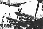 Liberator bomber crosses the shark-nosed bows of U.S. P-40 fighter planes