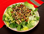 This photograph depicts a mixed greens salad toppe