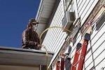 A weatherization worker blows sidewall insulation