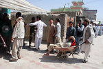 A man who is not able to walk is taken to a voter station in handcart in ninth police district in Kabul.