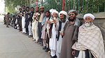 Residents line up in front of a polling center in Ghor province province.