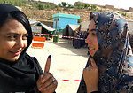 Two Afghan women talk after casting ballots in Ghor province.