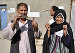 An elderly woman and her son after casting their votes show their fingers and voting cards to media in front of a polling station in 13th police district of Kabul province.