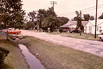 This 1974 photograph depicts a roadside drainage d