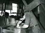 This photograph shows a man polishing, or 'pouncin