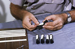 A CDC field researcher is shown here labeling glas