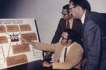 This image shows three systems analysts discussing