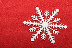 Snowflake on red glittery background