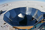 A photograph of the en:QUaD telescope inside its groundshield taken from a crane above the telescope. The telescope structure consists of a en:cassegrain optical system mated to the existing DASI mount surrounded by a reflective groundshield which limits