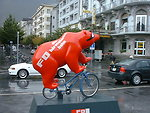 A bear on a bicycle outside Brig station, Wallis, Schweiz advertising the Furka-Oberalp-Bahn (English) or Furka-Oberalp-Bahn (German) on a wet day.