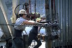 Oil rig workers picking up a drill pipe joint