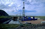 Oil drilling rig (foreground), lined reserve pit to the left of drilling rig, workover rig (smaller, in background)