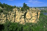 Sun shining on the sandstone cliffs in the Four Dances Natural Area with the Yellowstone River and Billings MT in the background