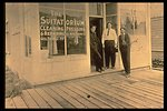 "Black and white photo of men posing in front of the ""Suitatorium"" store."
