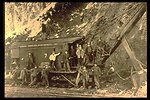 Black and white photo of workers posing on a steam shovel.