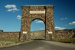 The Roosevelt Arch is located in Montana at the North Entrance of Yellowstone National Park. The arch's cornerstone was laid by Theodore Roosevelt. The placard reads 'For the Benefit and Enjoyment of the People.'