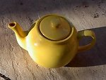 A yellow ceramic teapot against a stone floor, taken by CGS. Public domain.   en:Commons:Category:Yellow en:Commons:Category:Teapots
