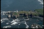 Aerial view of Yaquina Head lighthouse and parking area.