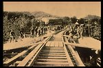 Black and white photo of rail workers on a railroad track working/posing.