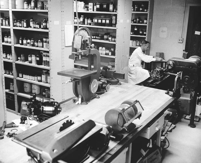 This historic 1963 photograph depicted a technician inside a storage room, which also acted as a machine shop on the Centers for Disease Con