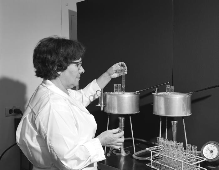In this 1965 image, a laboratory technician was checking for the presence of a color change in a test using the Benedict method.