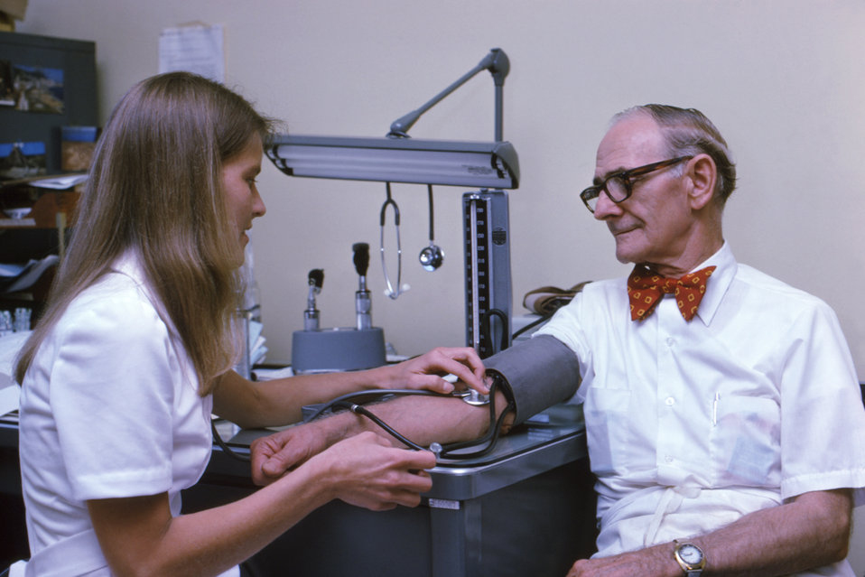 This photograph shows a patient having his blood pressure read by a public health practitioner.